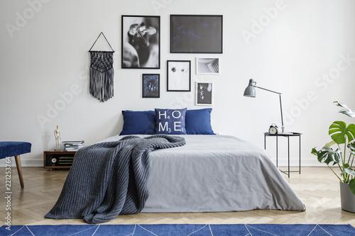 Koc na łóżku z niebieskimi poduszkami w sypialni białe wnętrze z galerii i lampa na stole. Prawdziwe zdjęcie