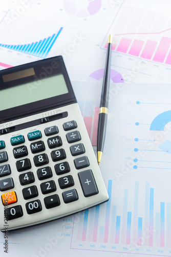 Calculator and Pen with Business Graphs finance document. - 221258945