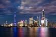 Leinwanddruck Bild - Die hell beleuchtete Skyline von Shanghai am Abend mit bewölktem Himmel, China