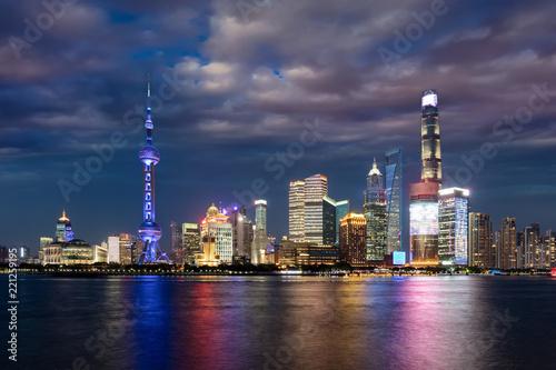 Leinwanddruck Bild Die hell beleuchtete Skyline von Shanghai am Abend mit bewölktem Himmel, China