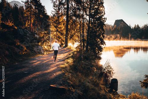 Athlete trail running in High Tatras during sunrise.