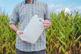 Farmer holding pesticide chemical jug in cornfield - 221270147