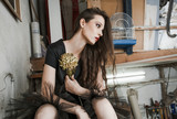 young fashion woman in  black dress in  artist studio sit on stairs hold big flower - 221271753