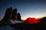 Night bivouac at Tre Cime di Lavaredo, milion star hotel under night sky, red illuminated tent on pass in Dolomites, Italy. - 221273940