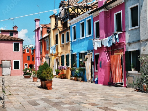 Street with colorful houses, flowering plants in Venice, on the island of Burano, Hanging on the windows and drying clothes