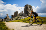 Tourist cycling in Cortina d'Ampezzo, stunning rocky mountains on the background. Woman riding MTB enduro flow trail. South Tyrol province of Italy, Dolomites. - 221274742
