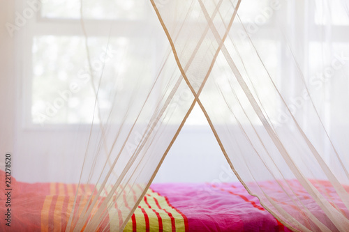 Bed with colorful quilt under a mosquito net - 221278520