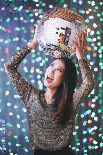 Portrait of excited happy young woman posing with discoball - 221278533