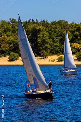 Yachts sail along the shore