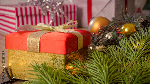 Closeup image of golden gift box with ribbon bow with Christmas decorations on wooden floor