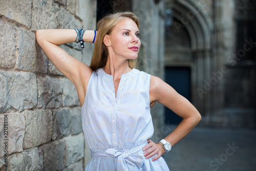 Leinwanddruck Bild smiling woman near the stone wall