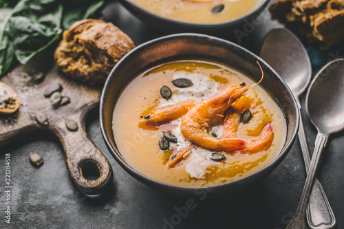 Autumn pumpkin creamy soup in bowls - 221284518