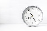 Silver wall clock on white wooden desk - 221289544