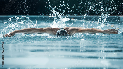 Leinwandbild Motiv The dynamic and fit swimmer in cap breathing performing the butterfly stroke at pool. The young man. The fitsport, swimmer, pool, healthy, lifestyle, competition, training, athlete, energy concept