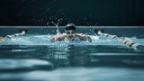 The dynamic and fit swimmer in cap breathing performing the butterfly stroke at pool. The young man. The fitsport, swimmer, pool, healthy, lifestyle, competition, training, athlete, energy concept - 221292110