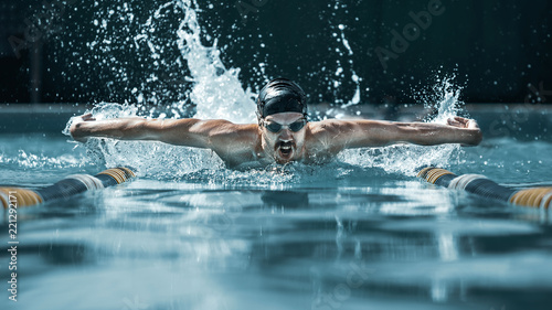 Leinwanddruck Bild The dynamic and fit swimmer in cap breathing performing the butterfly stroke at pool. The young man. The fitsport, swimmer, pool, healthy, lifestyle, competition, training, athlete, energy concept