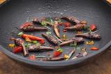 Insekten gebraten in der Bratpfanne mit Kräutern, Tomaten und Peperoni - 221301538