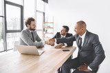 multiethnic smiling businessmen shaking hands at meeting at workplace with laptop - 221301942