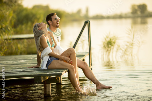 Poster Romantic couple sitting on the wooden pier on the lake