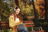 Young woman enjoys music through the headphones in the park - 221313355