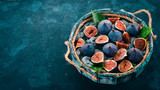 Fresh figs in a wooden box on a blue background. Free space for text. Top view. - 221316566