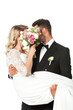 young newlyweds covering faces with bridal bouquet while groom carrying bride isolated on white