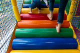 Colorful stairs in children play house, with child legs climbing up closeup - 221321395