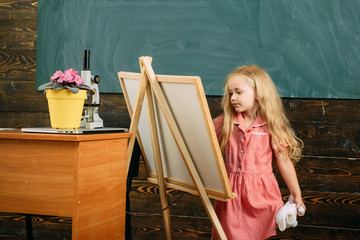 Small child painting picture on studio easel. Girl in painting studio