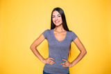 Young attractive cute brunette woman in gray T-shirt is posing and looking on camera isolated over yellow wall - 221325308