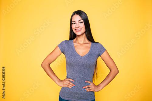 Młoda atrakcyjna śliczna brunetka kobieta w szarej koszulce pozuje i patrzeje na kamerze odizolowywającej nad żółtą ścianą