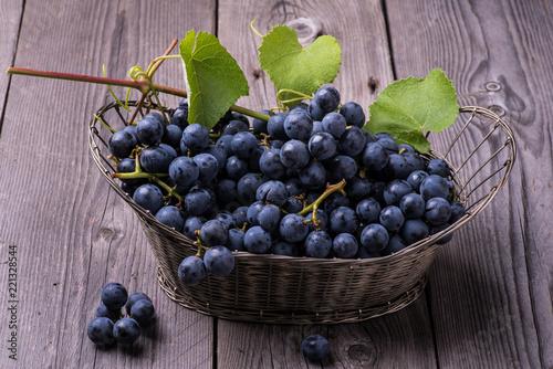 natura morta con uva nera in un vecchio cestino di metallo - 221328544