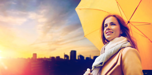 season, weather and people concept - beautiful happy young woman with yellow umbrella over sunset in autumn city of tallinn background