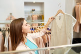 shopping, fashion, sale and people concept - young woman choosing shirt in mall or clothing store - 221330918