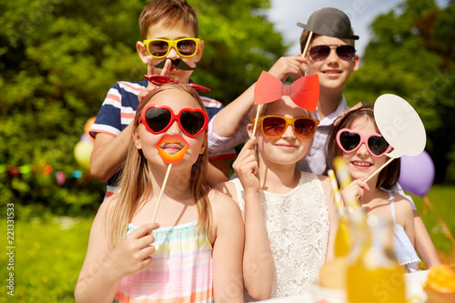 holidays, childhood and celebration concept - happy kids with party props on birthday in summer garden - 221331533