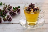A сup of fragrant tea with fresh oregano on the white wooden table. - 221332554