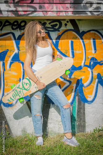 Portrait of young beautiful woman wearing white tank shirt and blue jeans on brick wall with graffiti background