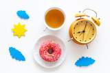 Time for breakfast concept. Tea, donut near alarm clock, sun and clouds cutout on white background top view - 221340192