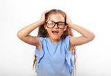 Anger young studing kid girl in glasses strong screaming with wild open mouth and holding head the hands on white background - 221357955