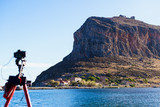 Camera on tripod and Monemvasia island - 221359540