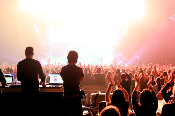 Sound and lighting technicians and the crowd in a concert
