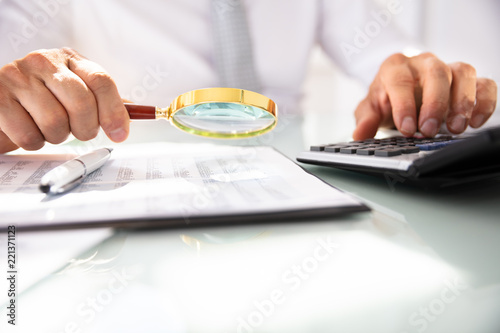 Businessman Analyzing Financial Report With Magnifying Glass - 221371123