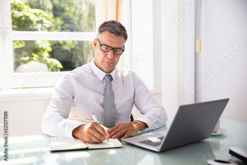 Foto Murales Businessman Writing Schedule In Diary With Pen