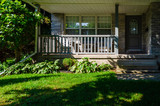Shady covered front porch on a gray brick house - 221371509