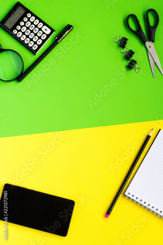 Different black stationery, notepad and phone on creative yellow-green background. Top view, flat lay - 221372981