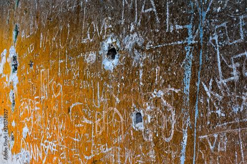 Graffiti on abandoned stone wall, orange lichen