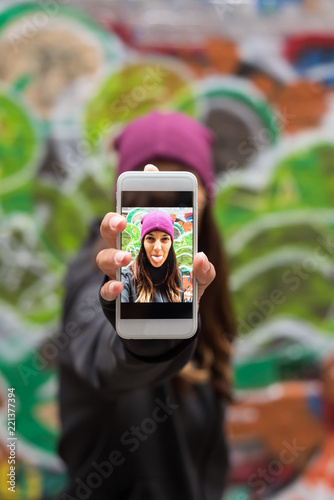 Young woman smiling and taking a selfie with her smartphone
