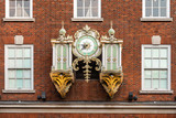 Red bricks facade with an aincient decorated wall clock surrounded by white windows - 221385707
