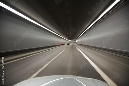 Schnelle Fahrt im Auto durch einen Tunnel - 221386504