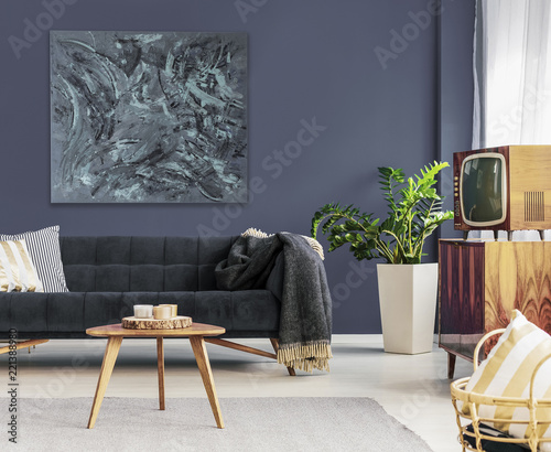 Television on cabinet near table and couch in dark living room interior with painting. Real photo © Photographee.eu