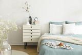 A bright bedroom interior with sage green and white bedding, pillows on bed and a drawer nightstand. Real photo.